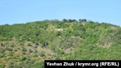 На склонах сохранились два ряда столбов с колючей проволокой