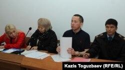 Подсудимый Асет Абишев (второй справа) рядом со своим адокатом Гульнарой Жуаспаевой перед началом судебного процесса по его делу. Алматы, 16 октября 2018 года.