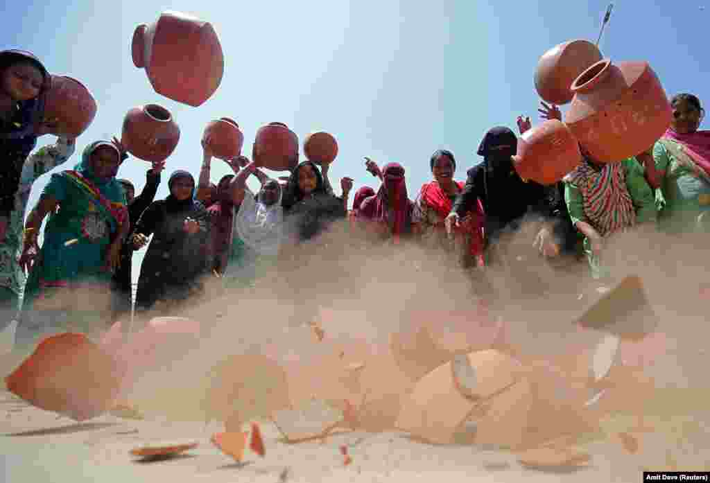 Women throw earthen pitchers onto the ground in protest against a shortage of drinking water in Ahmedabad, India. (Reuters/Amit Dave)