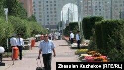 Пешеход идет по тротуару, вдоль которого выстроились полицейские. Астана, 18 июля 2010 года.