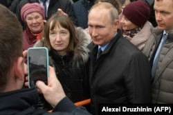 Russian President Vladimir Putin poses for pictures with a member of the public. (file photo)