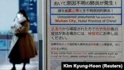 Женщина в маске проходит мимо информационного стенда о вспышке коронавируса в Ухане, Китай, в зоне прилетов аэропорта Ханеда в Токио, Япония. 20 января 2020 года.