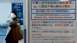 O femeie care a sosis Japonia trece pe lângă anunțul privind carantina instituită pentru călătorii care vin din Wuhan, centrul noii epidemii