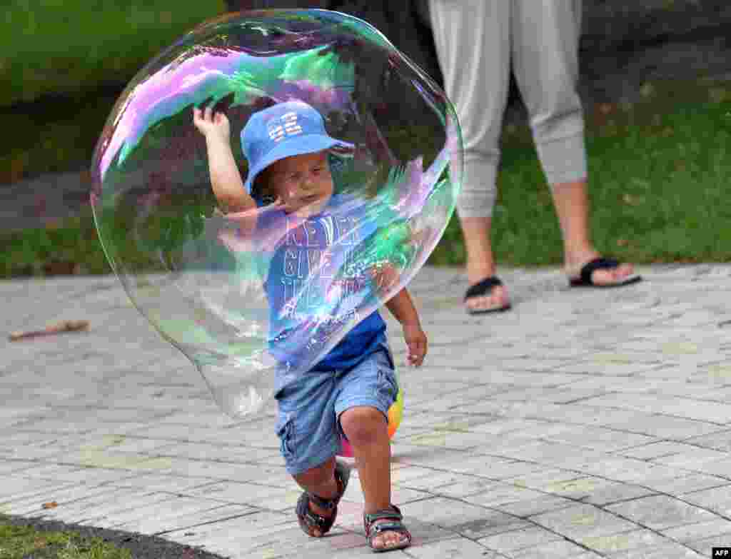 A boy plays with a soap bubble in one of Kyiv's parks on a hot day in the Ukrainian capital. (AFP/Sergei Supinsky)