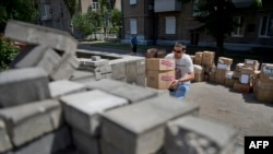 "A man carries boxes containing food and medical supplies received as humanitarian aid at the self-proclaimed ""Donetsk People's Republic"" administration headquarters in Donetsk in June."