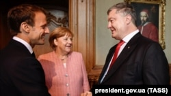 Президент Франции Эммануэль Макрон (слева), канцлер Германии Ангела Меркель и президент Украины Петр Порошенко. Ахен, 10 мая 2018 года.