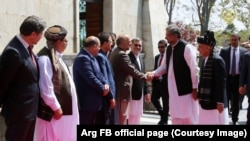 Abbasi (right) shakes hands with Afghan officials in Kabul.