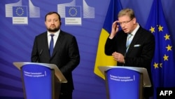 Ukrainian Deputy Prime Minister Serhiy Arbuzov (left) and European Commissioner for Enlargement and European Neighborhood Policy Stefan Fuele appear at a joint press conference in Brussels on December 12.