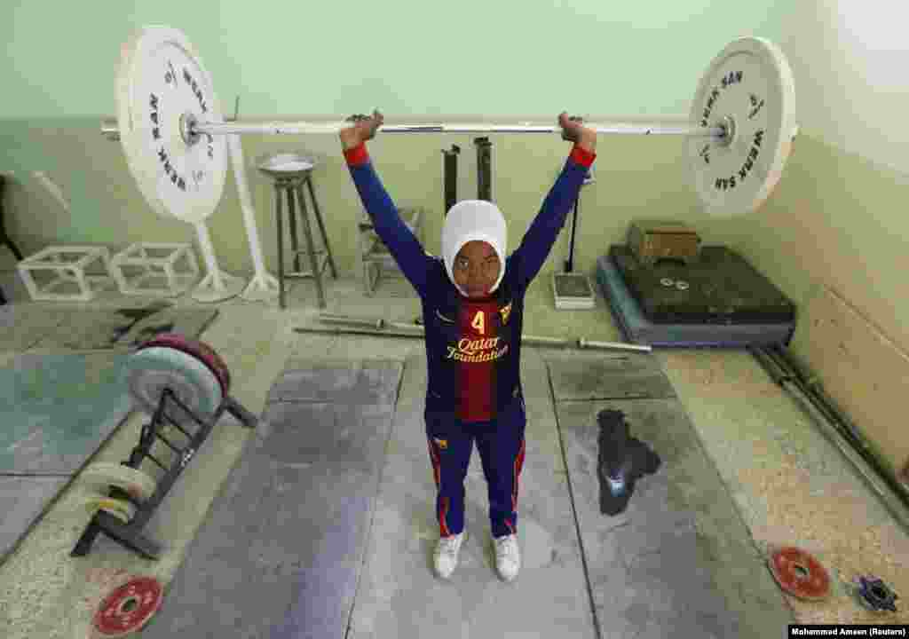 A member of Iraq's first female weightlifting team hoists a barbell at a gym in Baghdad's Sadr City neighborhood on April 28 while training for the Asian Championships in Qatar.