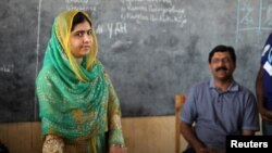 Pakistani Nobel Peace Prize laureate Malala Yousafzai (left) and her father, Ziauddin Yousafzai, speak in a classroom in Rwanda.