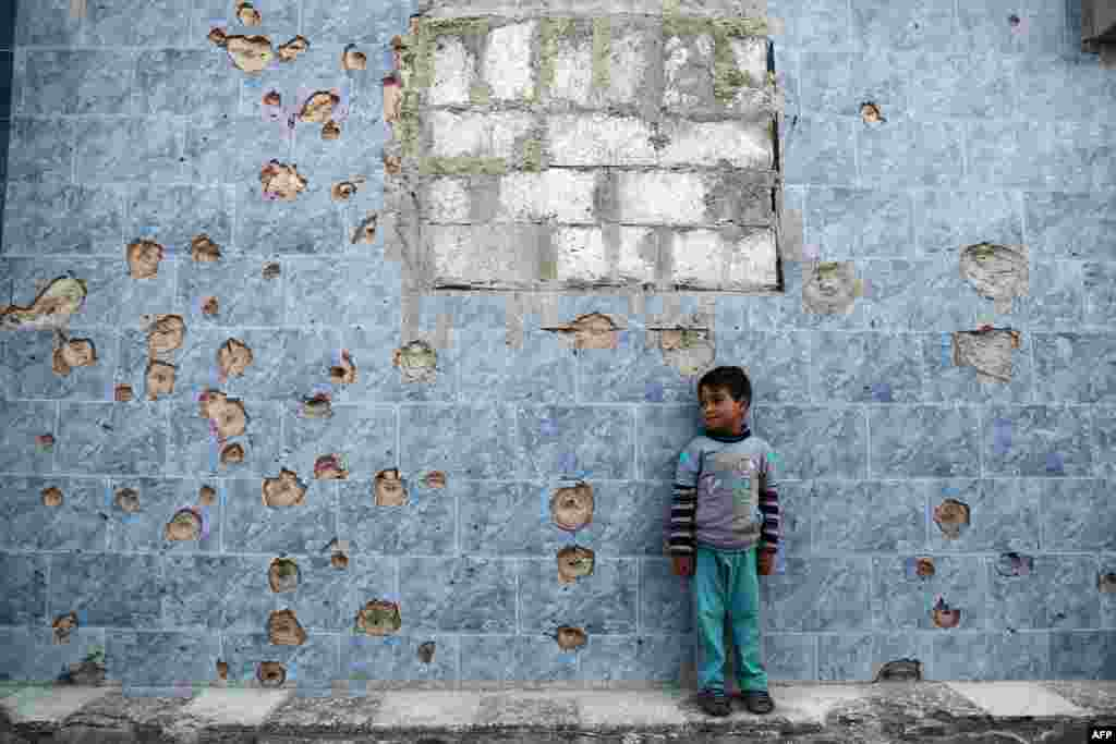 A Syrian boy stands against a bullet-riddled wall in the rebel-held town of Douma, on the eastern outskirts of the Syrian capital, Damascus. (AFP/Abd Doumany)