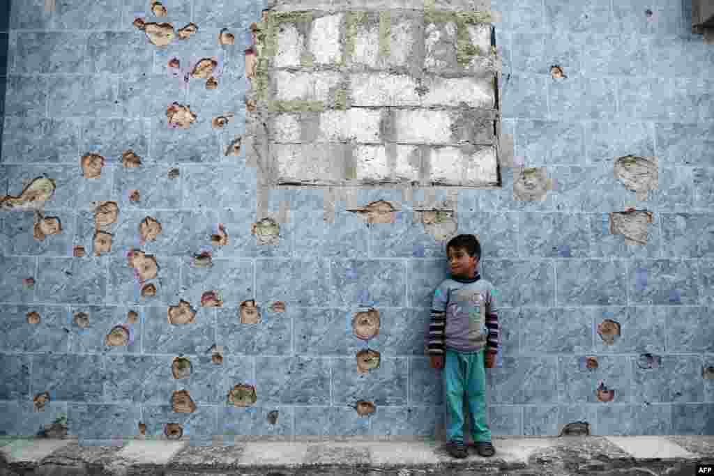 Сырыйскі хлопчык стаіць супраць пабітай кулямі сьцяны на ўсходняй ўскраіне сырыйскай сталіцы Дамаску, якая знаходзіцца пад кантролем паўстанцаў.