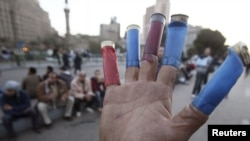 Egypt -- A protester places empty shotgun shells on his fingers during an anti-government protest in Tahrir square in Cairo, 31Jan2011
