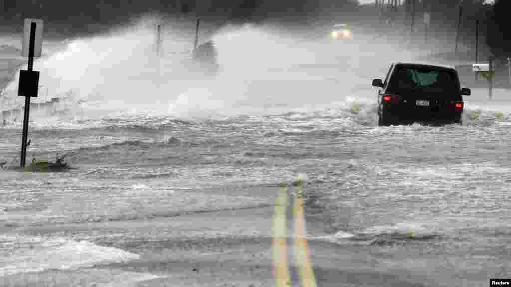 A car drives through water driven onto a roadway by Hurricane Sandy in Southampton, New York.