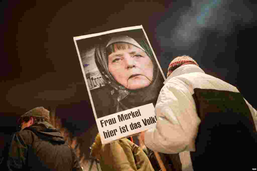 A participant in a rally with the anti-Islamic Pegida movement holds up a picture of Chancellor Angela Merkel wearing a head scarf. Islam is part of German life, Merkel said on January 12, even as a group of anti-Islam and anti-refugee protesters geared up for controversial marches that have become a weekly fixture in the eastern city. (epa/Arno Burgi)