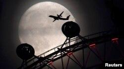 Літак пролітає повз оглядове колесо «Лондонське око» на тлі «супермісяця», Лондон, Велика Британія, 13 листопада 2016 року