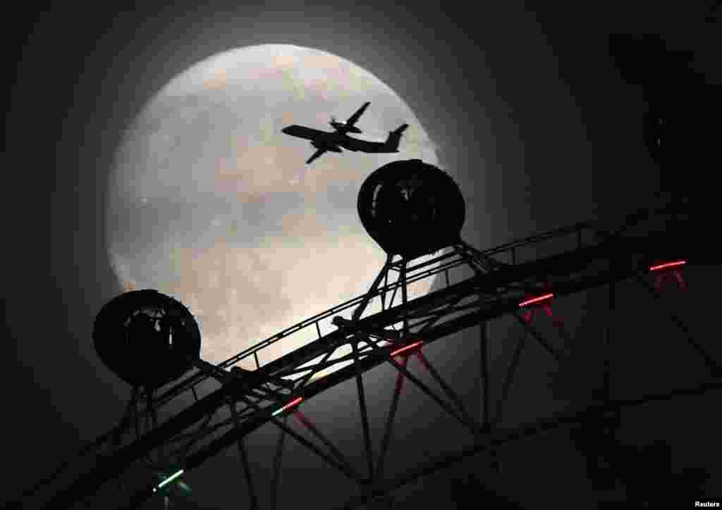 Лондондағы London Eye аттракционының үстінен ұшып бара жатқан ұшақ пен жарық ай