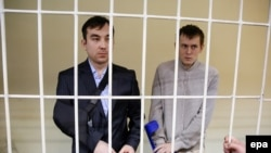 Aleksandr Aleksandrov (right) and Yevgeny Yerofeyev stand in a defendants' cage as they attend a court hearing in Kyiv in September.