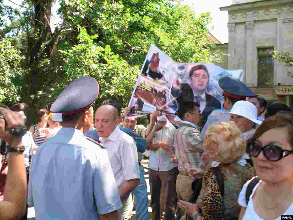 Полицейские отбирают плакаты у участников акции протеста. - Полицейские вначале решили отбирать плакаты у участников акции протеста, но встретили сопротивление. Алматы, 24 июня 2009 года.