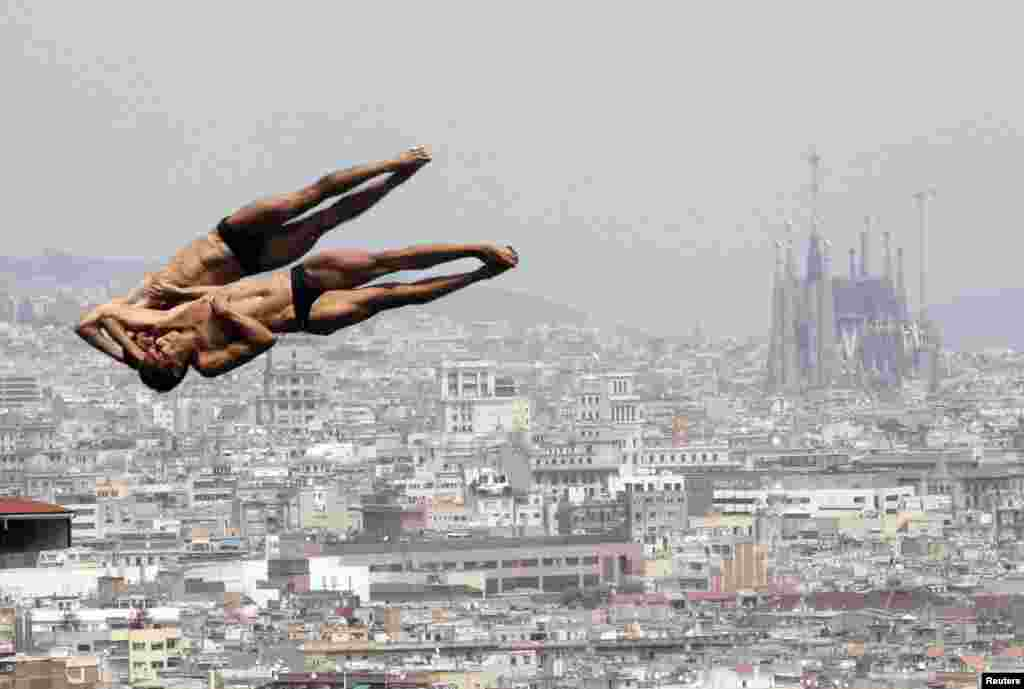 Mexico's Ivan Garcia and German Sanchez perform a dive during a practice for the men's synchronised 10-meter platform event with a backdrop of the Sagrada Familia Cathedral at the Montjuic municipal pool in Barcelona. (Reuters/Albert Gea)