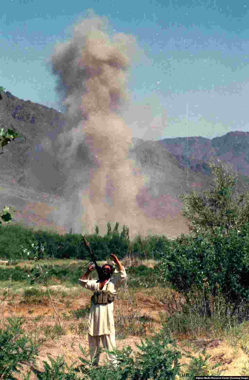 A mujahedin fighter scans the sky after an air strike. As conditions became increasingly risky for foreign journalists inside Afghanistan (in 1984 a Soviet diplomat vowed any journalist caught with mujahedin fighters would be killed), Washington also funded a controversial program to supply Afghan rebels with cameras.