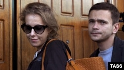 Opposition leaders Ksenia Sobchak and Ilya Yashin arrive for questioning at a Federal Investigative Commision building in Moscow, 12Jun2012