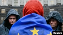 Ukraine -- A protester wrapped in a EU flag attends a rally to support EU integration as police stand guard in front of the cabinet of ministers building in Kyiv, November 25, 2013