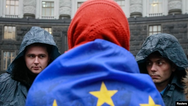 A protester wrapped in a EU flag attends a rally to support EU integration in Kyiv on November 25.