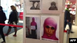 People walk past an information banner with the photos of terrorism suspects in a department store in the Russian Black Sea resort of Sochi on January 18.