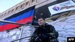 Ýaragly adam separatistler tarapyndan eýelenen regional binany gorýar, Slowýansk, 25-nji aprel, 2014.
