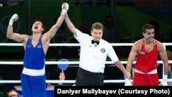 Казахстанский боксер Данияр Елеусинов (слева) радуется победе над Шахрамом Гиясовым из Узбекистана в финальном поединке Олимпиады в Рио-де-Жанейро. 17 августа 2016 года.
