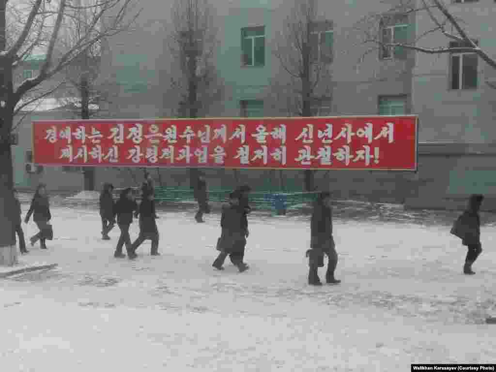 Жители, спешащие ранним утром на работу, идут мимо надписей с партийными лозунгами.