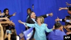 Хиллари Клинтон жана ага шайлоодо вице-президенттикке талапкер катары өнөктөш боло турган сенатор Тим Кейн Флорида Эл аралык университетиндеги жыйынга келген учур. Майами, 23-июль, 2016-жыл.