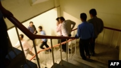 Pakistanis leave an office building after an earthquake in Karachi on September 24.