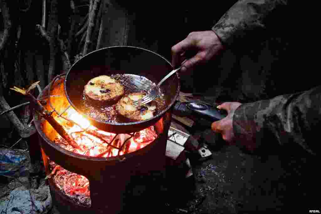 A soldier has made himself buns soaked in egg yolk for lunch. The buns are are heated over a wood-burning stove after being soaked.