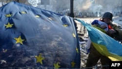 An antigovernment opposition activist places European Union and Ukrainian flags side by side at a barricade in the Ukrainian capital of Kyiv on February 2 as tens of thousands of protesters rallied to demand President Viktor Yanukovych resign.