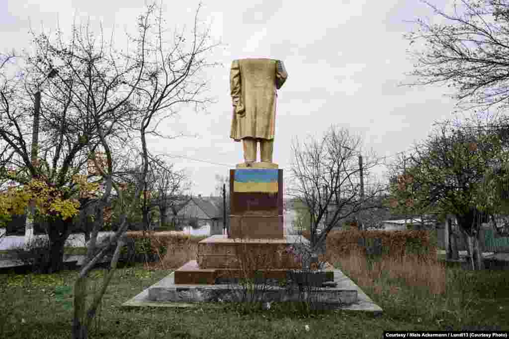 A headless Lenin stands in Shabo, spray-painted with the colors of the Ukrainian flag.