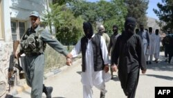 A member of the Afghan security forces escorts alleged Islamic State fighters being presented to the media at the police headquarters in Jalalabad on May 29.