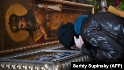 Вірянка цілує раку з мощами св. Макарія, митрополита Київського, Володимирський собор, Київ, 13 березня 2020 року