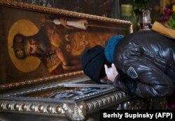 Вірянка цілує раку з мощами св. Макарія, митрополита Київського. Володимирський собор, Київ, 13 березня 2020 року