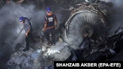 Rescue workers search for survivors amid the wreckage of the passenger plane that crashed in Karachi on May 22.