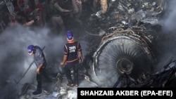 Rescue workers search for the bodies or survivors amid wreckage of a passenger plane of state-run Pakistan International Airlines after it crashed in residential part of Karachi on May 22.