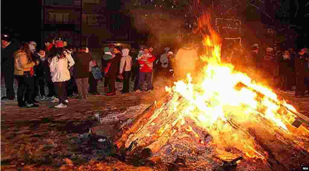 Рождественский костер в столице Македонии Скопье. На Балканах встречается обычай разжигать небольшие костры во дворах домов под Рождество, перешагивать через угли для здоровья, благополучия. Считается, что костры разжигают для того, чтобы согреть новорождённого Христа. Костры из пней горят и тлеютв течение нескольких дней, собирая вокруг себя соседей и гостей за бокалом вина с приготовленными на углях блюдами.
