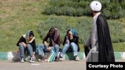 Мужчина проходит мимо сидящих на улице девушек. Иран. Иллюстративное фото.