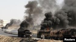 Загоревшиеся в ходе военных столкновений грузовики рядом с городом Алеппо, Сирия. 27 августа 2012 года.