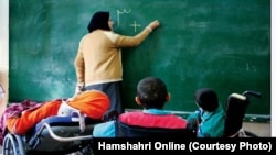 Iran -- An Iranian teacher teaching mathematics in a special school for kids with special needs, undated.