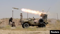 Iraq -- Members of Iraq's Shi'ite paramilitaries launch a rocket towards Islamic State militants in the outskirts of the city of Falluja, in the province of Anbar, IJuly 12, 2015
