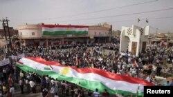علم كردي كبير يرفعه متظاهرون في خانقين