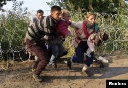 Migranţi sirieni, trecând de gardul de sârbă din Ungaria (de la graniţa cu Serbia), în apropiere de Roszke, 27 august 2015