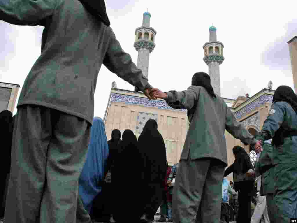Полицейские охраняют афганских женщин, собравшихся на акцию протеста против нового закона о браке, который резко ограничивает права женщин